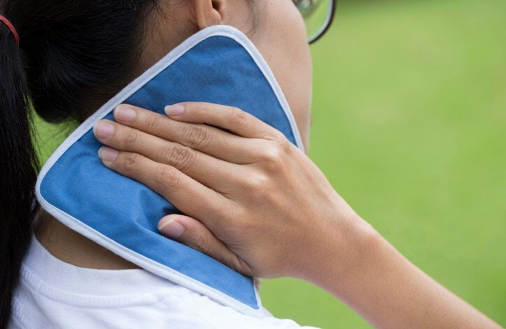 A closeup of the backside of a woman holding an ice pack to her neck. Common treatment for whiplash includes applying heat or ice to the neck area.