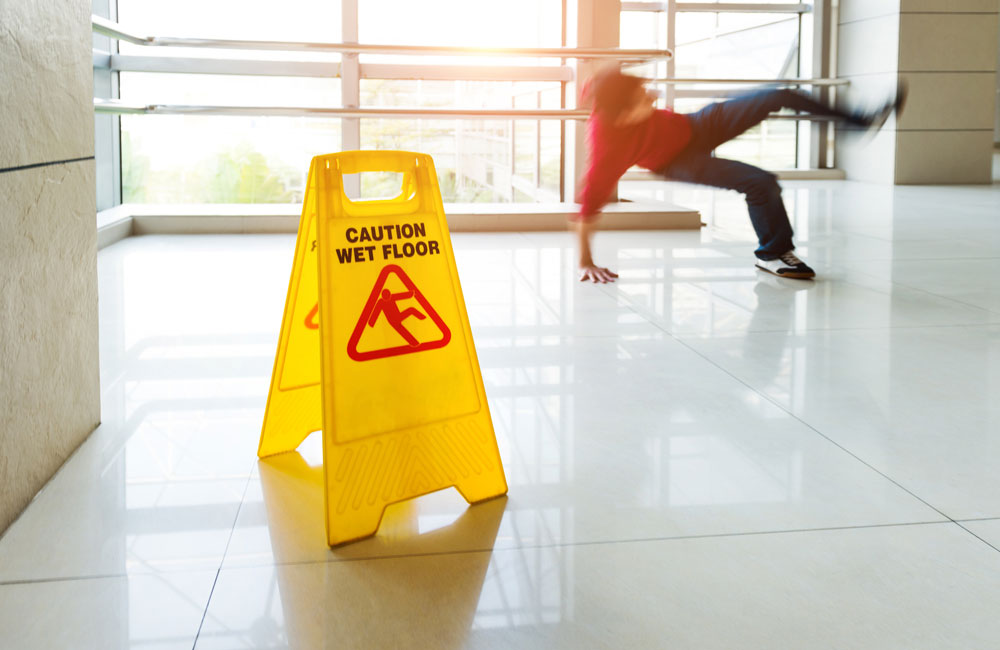 Man in red slips on floor in building near a Wet Floor sign