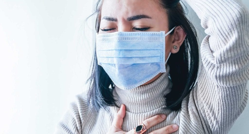 Woman in mask and white sweater struggling to breathe