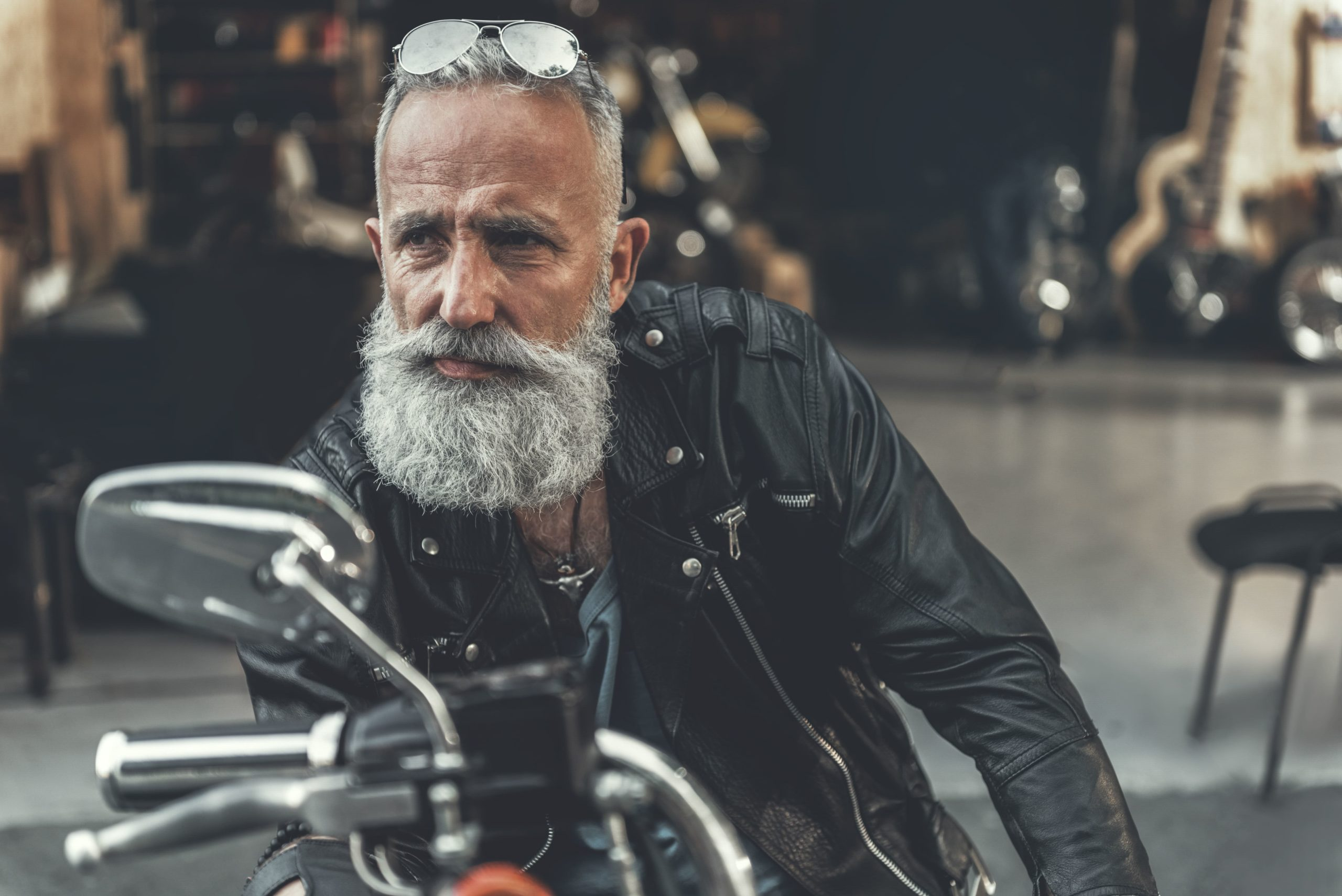 A man with a graying beard sits on his motorcycle with raised sunglasses and looks into the distance.