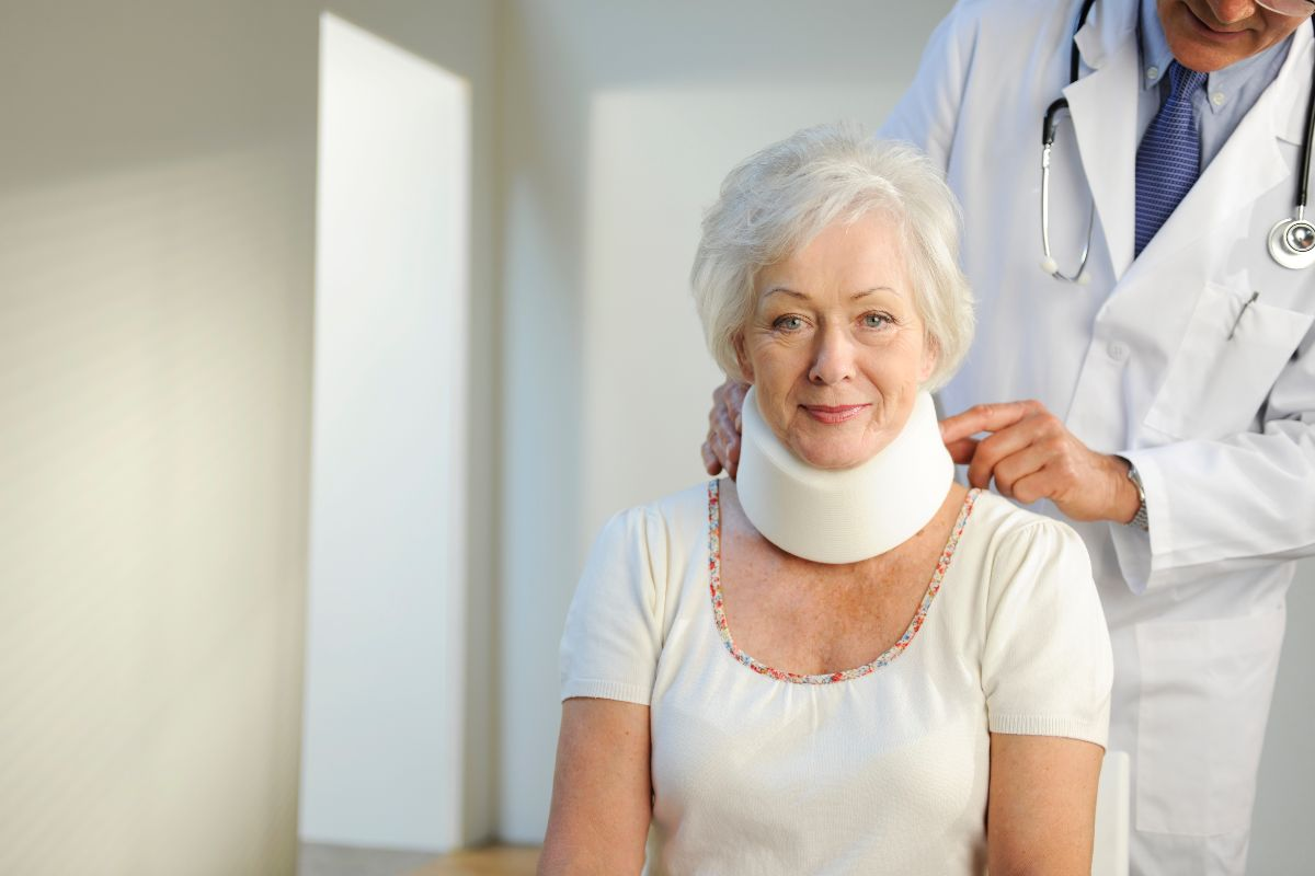Elderly woman in a neck brace gets a checkup at the doctor